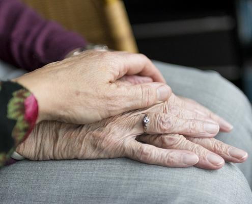 jonge hand ligt op oude hand